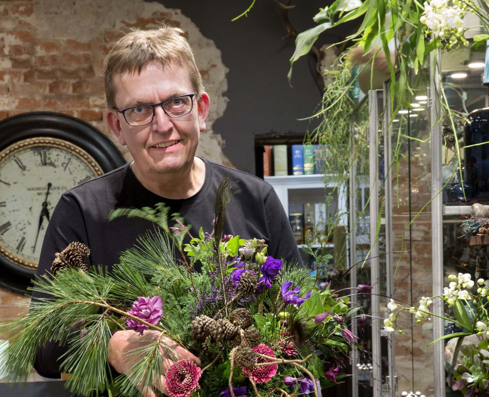 Per Kaspersen står i sin butik med en buket blomster i hånden
